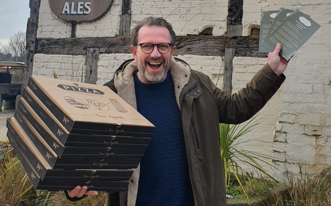Publican outside his out holding pizza take away boxes and some Winter Warmers poems